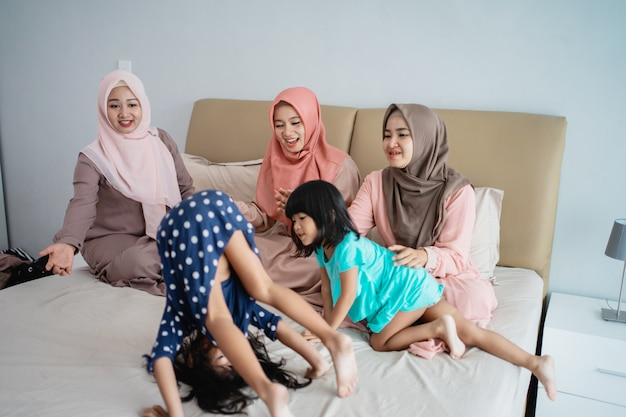 Three muslim woman enjoy playing with her daughter in the bedroom