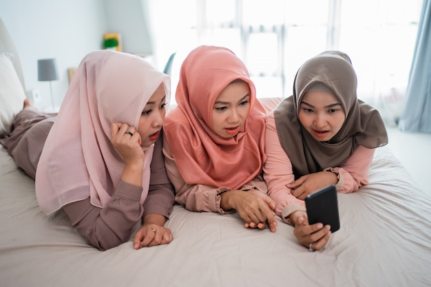 Три мусульманки лежат и наслаждаются использованием смартфона на кровати