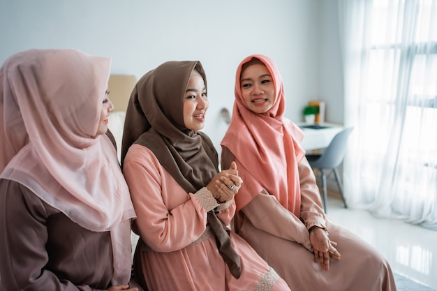 Three muslim women chatting while sitting on the bed