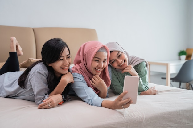 スマートフォンを使用してビデオ通話をしながらベッドに横たわっている3人のイスラム教徒の女性