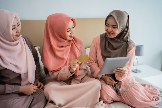 Three muslim women using tablet for buy the items in the online store