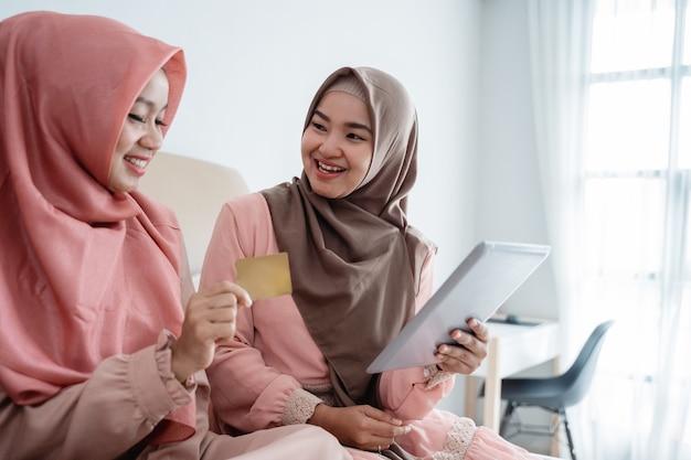 家にいるときにタブレットを使用してオンラインストアでアイテムを購入する3人のイスラム教徒の女性