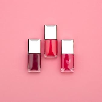 Три лака для ногтей на розовом фоне