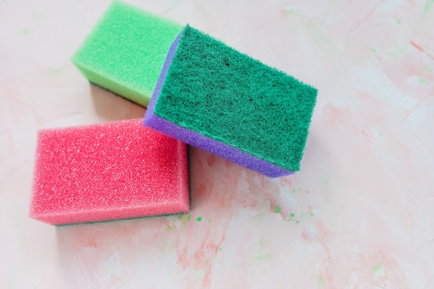 Three new colorful sponges for washing dishes on pink background. domestic household and cleaning