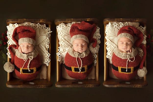 갓 태어난 세 형제는 엘프 복장을 한 유아용 침대에서 잠을 자고 있습니다. 고품질 사진