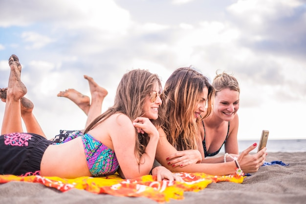 Три милые и красивые девушки на пляже лежат на песке, отдыхают на свежем воздухе, отдыхают под солнцем и делают селфи со смартфоном.