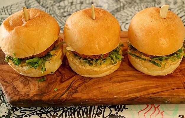 木製のブレッドボードに3つのおいしいチキンスライダーサンドイッチ