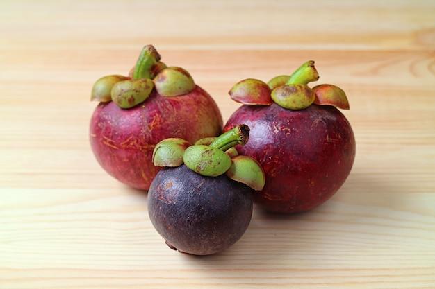 木製の表面にフルーツの女王として知られている新鮮な熟した紫色のマンゴスチンフルーツの3つ