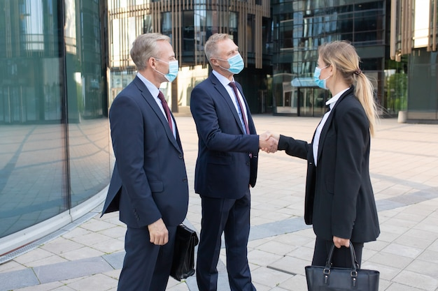 Three office workers in facial masks making deal or greeting. professional successful businesswoman and businessmen standing outdoors and handshaking. negotiation, protection and partnership concept
