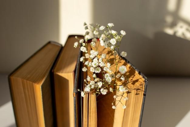 태양 빛에 테이블에 흰색 라든지 꽃과 세 오래 된 책