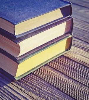 Три старые книги сложены стопкой на старом деревянном столе, квадратная рамка