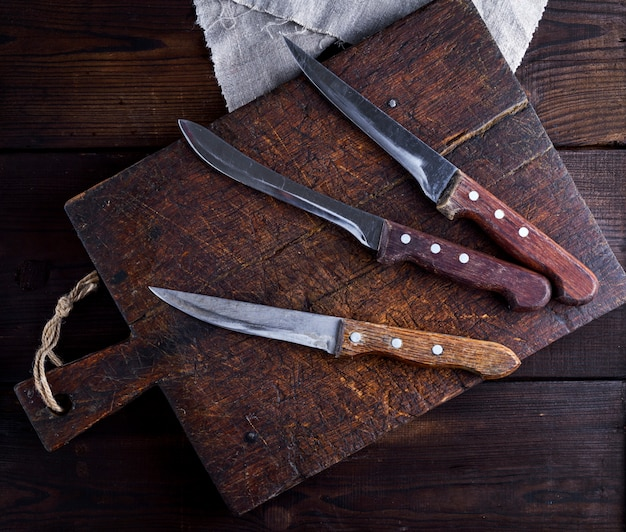Three old kitchen knives on a brown wooden cutting board