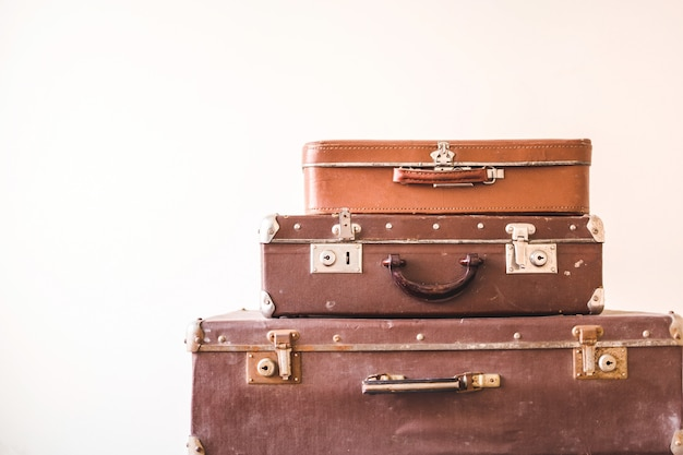 Three old vintage suitcases against a light wall background. rustic retro style