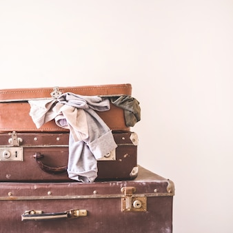 Three old vintage suitcases with clothes on a light wall background. rustic retro style