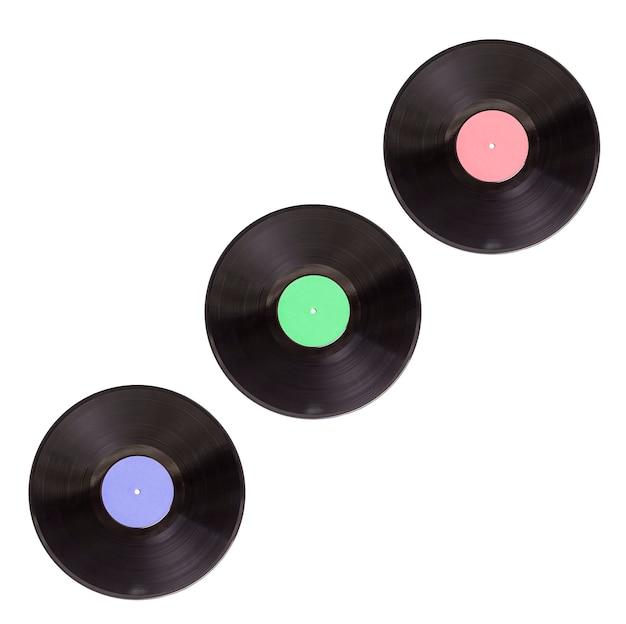 Три старые виниловые пластинки разных цветов на белом фоне