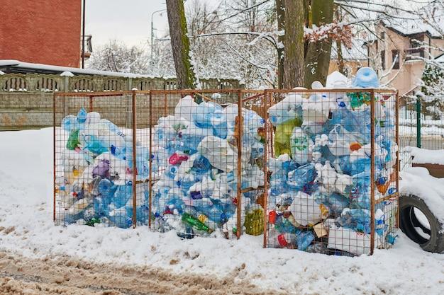 Три открытых мусорных бака с пластиковыми бутылками и пакетами. пластиковые отходы в больших мусорных баках. городская свалка на зимней улице.