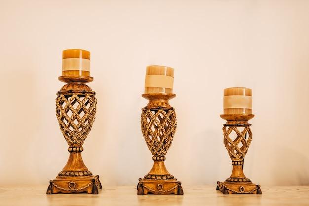 밝은 배경에 행에 베이지 색 촛불이있는 다양한 크기의 세 개의 투각 촛대