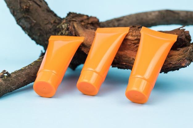 Три оранжевые кремовые трубки на старом дереве на синем фоне. косметика и лечебные мази на основе природных минералов.
