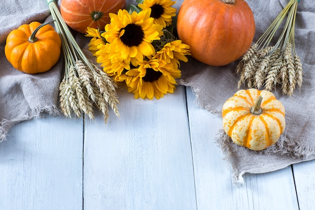 Three orange pumpkins, a bouquet of sunflowers, ears of corn on the bright wooden table