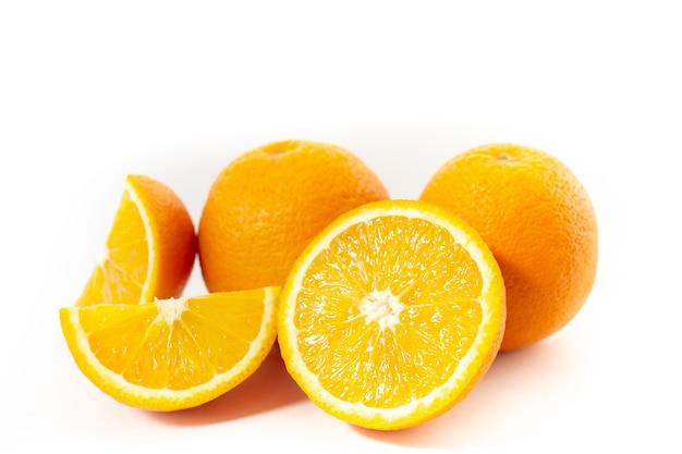 Три апельсина на белом фоне, разрезанный на три части (крупный план)