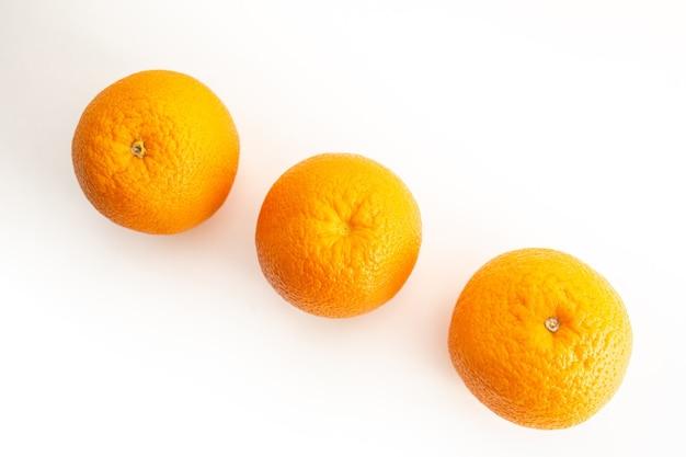 Три апельсина на белом фоне вид сверху