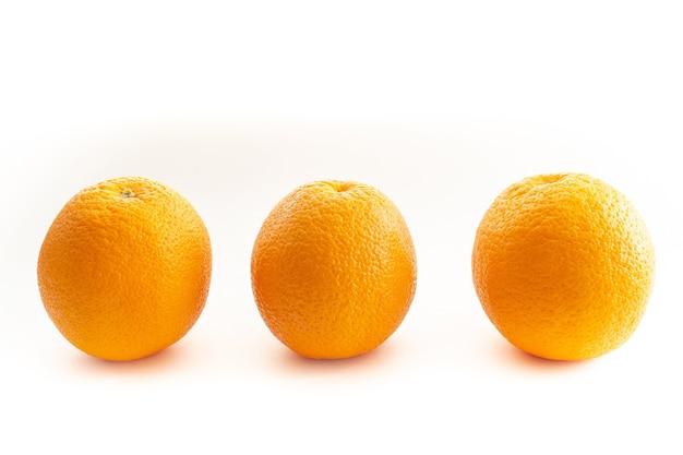 Три апельсина на белом фоне