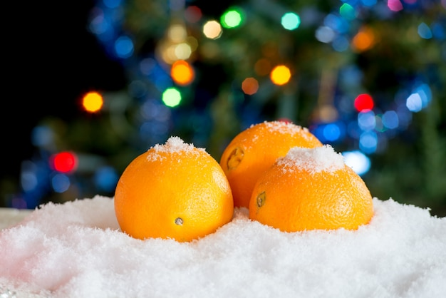 Three oranges in the snow with christmas decor