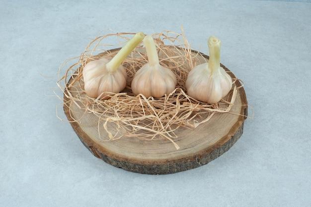 Tre aglio biologico sul pezzo di legno.