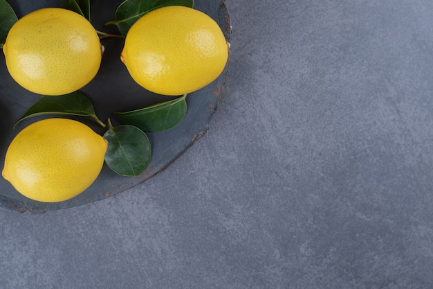 Three organic lemon on black board over grey background.
