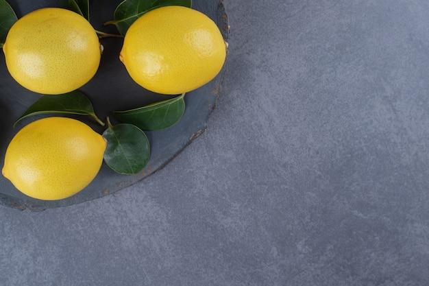 Три органических лимона на черной доске на сером фоне.
