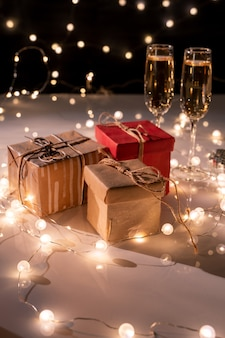 포장 된 선물 상자 3 개, 새해 파티를위한 조명 화환으로 장식 된 테이블에 샴페인 두 피리