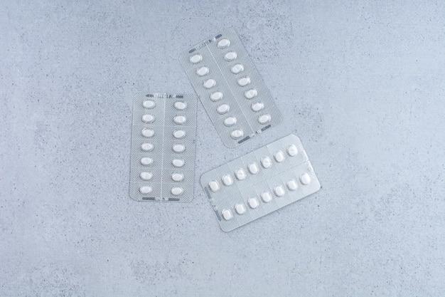 Tre confezioni di pillole mediche su marmo