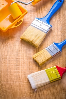 Three paint brushes roller and tray on wooden board