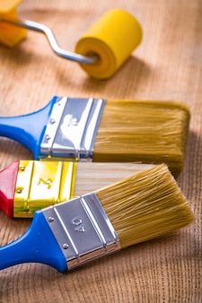Three paint brushes and roller on wooden board