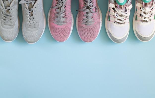 Вид сверху три пары спортивной обуви на голубом фоне с копией пространства