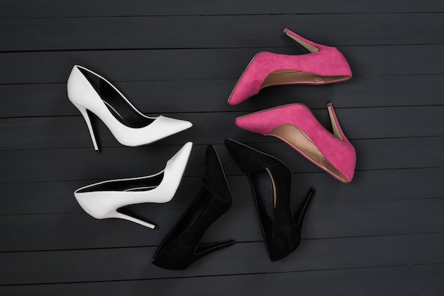 Three pairs of different high heel shoes. black wooden background.