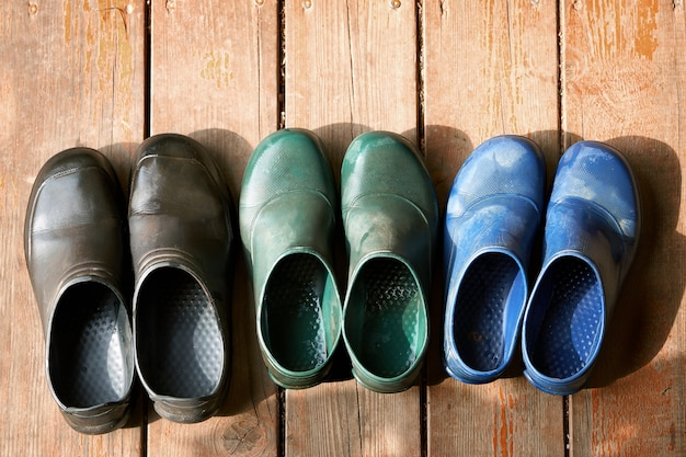 Three pairs of family rubber boots stand on the wooden floor. short rubber country goloshes