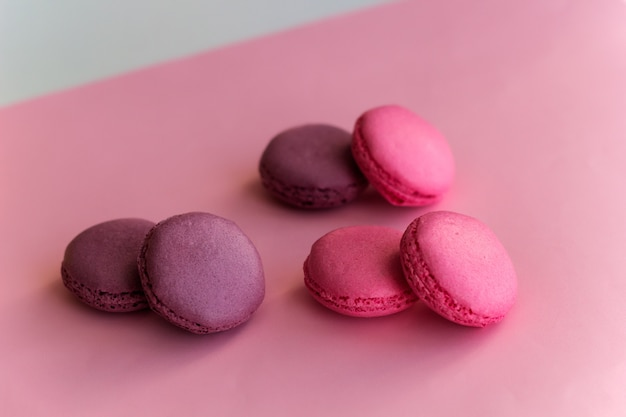 Three pairs of swet macaroons pink background