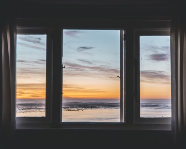 Three-paneled window with a beautiful view of the sunset outside