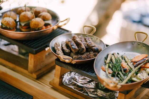 Три сковороды с сербскими колбасками, мини бургеры и овощи на плите