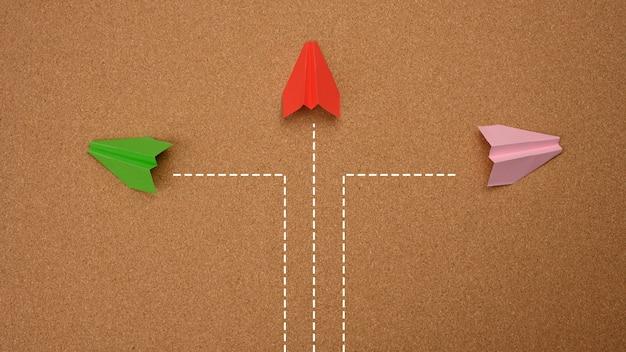 세 대의 종이 비행기가 갈색 배경에서 서로 다른 방향으로 날아갑니다. 결정의 개념, 생각의 불일치, 선택