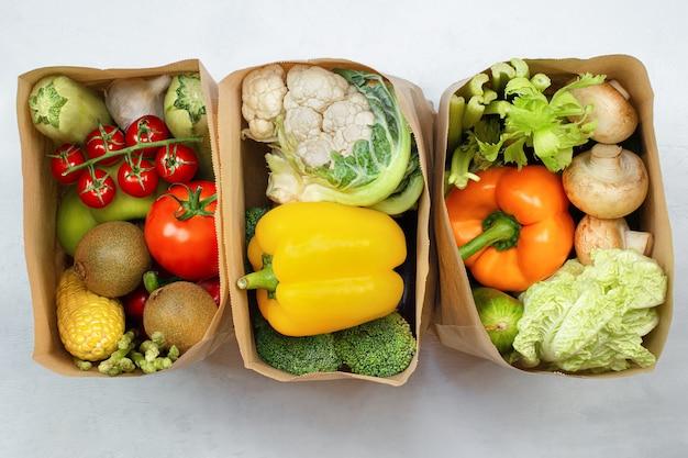ライトテーブル、上面図に新鮮な野菜や果物が入った3つの紙袋