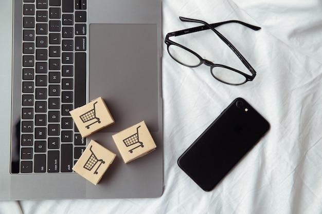 Три бумажные коробки или посылка на клавиатуре ноутбука в спальне. сервис покупок в интернете и доставка на дом