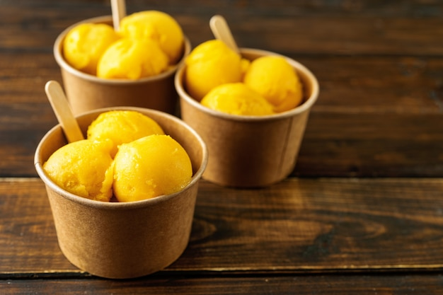 Three paper cups with mango sorbet