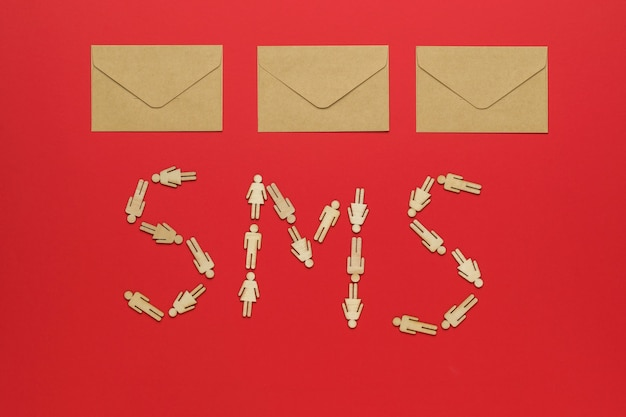 Three paper postal envelopes and an sms inscription made of wooden men on a red background. the concept of communication between people.