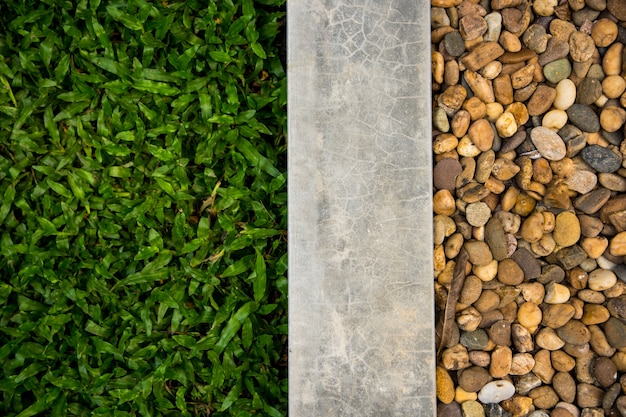 Three parts stripe decoration floor consist of grass, concrete and round rock.