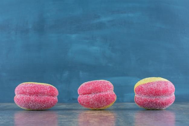 Tre biscotti a forma di pesca, sulla superficie di marmo.
