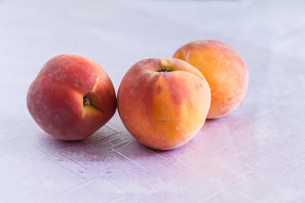 白いテーブルクロスに3つの桃