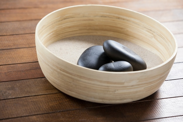 Three pebble stone on a wooden bowl