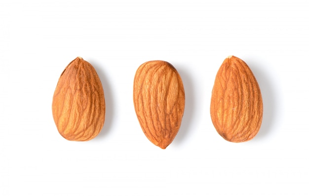 Three peeled almonds isolated on white background.
